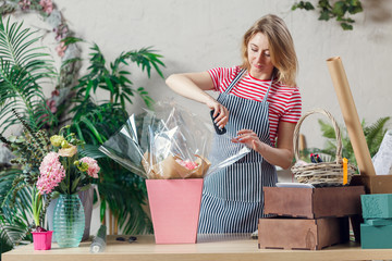 Image of young florist with stapler decorating floral composition at table with flowers, boxes
