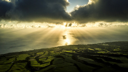 Aerial view on breathtaking landscape of Azores island - green fields, separated with trees. And amazing sky, sunset and Atlantic ocean on background. Sao Miguel, Portugal.