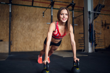 Portrait of spotswoman doing horizontal push-ups with kettlebells .