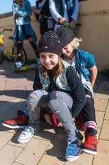 Laughing kids with skateboard on street