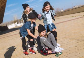 Playing kids riding skateboard on pavement