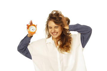 Portrait of a beautiful stressed woman holding clock in hands over white background