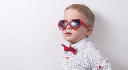 A small serious boy with glasses and a red bow tie is posing against the white wall.