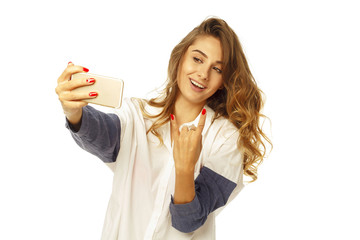Portrait of a beautiful young woman making selfie on smart phone and showing devil sign. Happy woman photographing herself.
