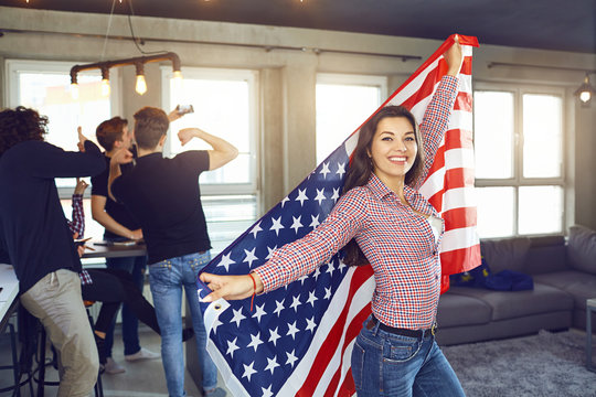 Girl with a beautiful smile with the flag of america indoors. Independence Day of the USA.