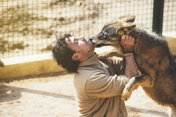 Man with wolf in zoo