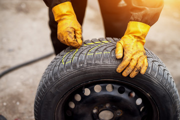 Mechanic with orange gloves is using chalk to mark tires while leaning on one in his workshop.