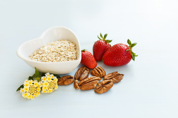 oatmeal in a plate in the shape of a heart, strawberry with a handful of pecans on a blue wooden background with a lantana flower at breakfast