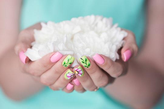 Руки с красивым маникюром и букет  цветов.