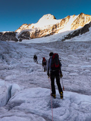 mountain guide leads his clients over a glacier on their way to a high alpine summit after an early morning start