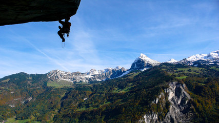 mountain guide on a large and overhanging roof lead and aid climbing a hard technical climb with a great background of blue sky and snow-capped peaks mountain landscape