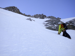 male mountain guide climbing a steep snow couloir on his way to a high summit in the Swiss Alps
