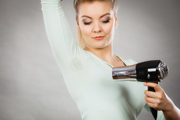 Woman drying armpit with hair dryer