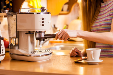 Woman in kitchen making coffee from machine