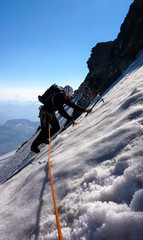 male mountain climber traversing a steep and exposed blank ice field on a high summit in the Alps
