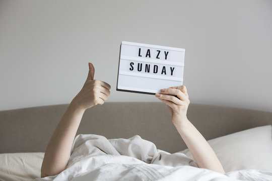 Female in bed under the sheets holding up a lazy sunday sign