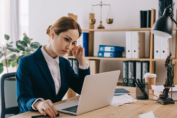female lawyer in suit working on laptop at workplace in office