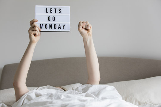 Female in bed under the sheets holding up a lets go monday sign
