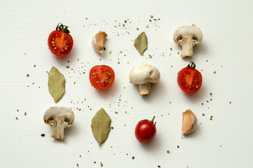 cherry tomatoes, champignons, bay leaves and garlic on a white background