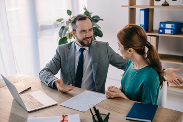 businessman and client discussing contract during meeting in office