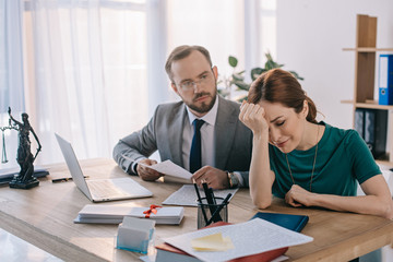 lawyer and client discussing contract at workplace with laptop in office