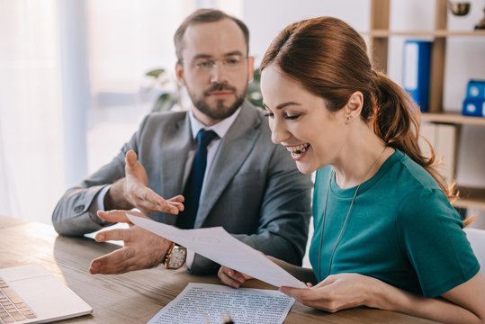 businessman and happy client discussing contract during meeting in office