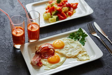 Breakfast from fried egg, bacon, vegetable salad and carrot juice. On a dark stone background