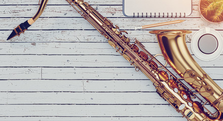The saxophone is placed on a wooden floor, a cup of coffee and notebook is placed on the wooden floor. Fotobehang