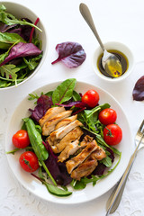 Sliced grilled chicken with green leaves salad on white plate