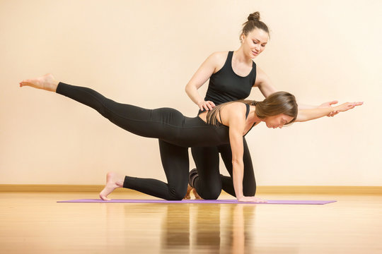 Yoga teacher is helping young woman to make asana poses at gym.