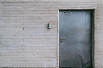 Metallic door with numeric lock on concrete wall