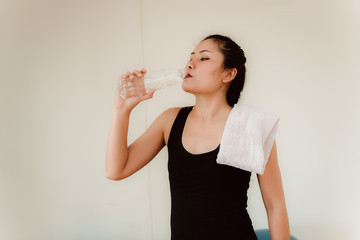 Portrait of beautiful woman drinking water after tworkout in fitness gym