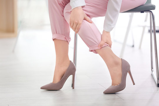 Young woman suffering from leg pain in office