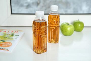 Bottles of apple juice on window sill