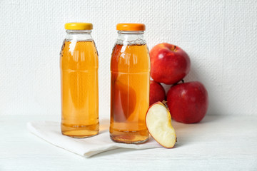 Bottles of apple juice on white table