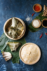 Asian rice piramidal steamed dumplings from rice tapioca flour with meat filling in banana leaves served in bamboo steamer. Ingredients and sauces above over blue texture background. Top view, space.