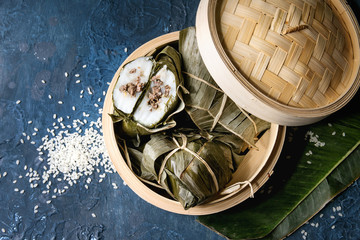 Asian rice piramidal steamed dumplings from rice tapioca flour with meat filling in banana leaves served in bamboo steamer with rice above over blue texture background. Top view, space.