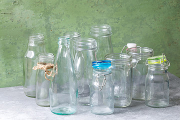 Variety of different shape empty opened glass bottles with and without lids standing on grey table with green wall as background.