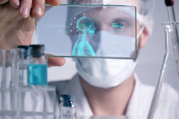 A physician, surgeon, examines a technological digital holographic plate represented the patient's body, the heart lungs, muscles, bones. Concept: Futuristic medicine, the human body, and the future.