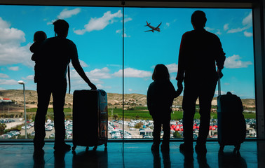 family with kids and luggage looking at planes in airport