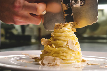 Egg pasta dish, typical Italian, with fine white truffle grated on top. Concept of: gourmet cuisine, truffles, Italian pasta, fine dishes.