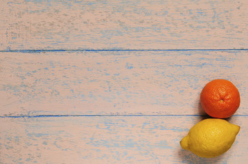 3803762 Orange mandarin and yellow lemon on a shabby old wooden background. View from above. Close-up, copy space