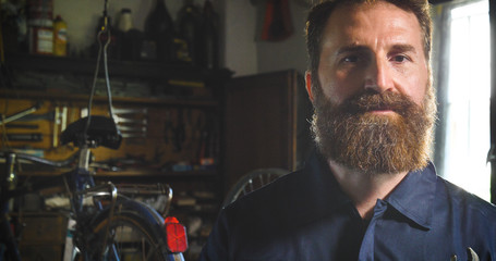 Well-groomed handsome bearded master hipster, specialist in bicycles, repairing a bicycle in his workshop, wheels, frame, spokes, the background of tools. Concept: pro bike, cycle passion, lifestyle.