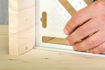 Construction, hand holding a square, setting a right angle between two boards.