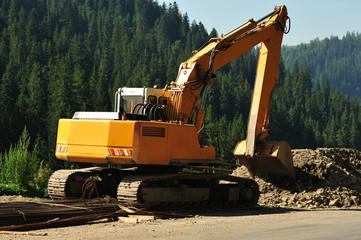 Big excavator at work on mountain road. Yellow excavator at work on the mountain road site under construction.