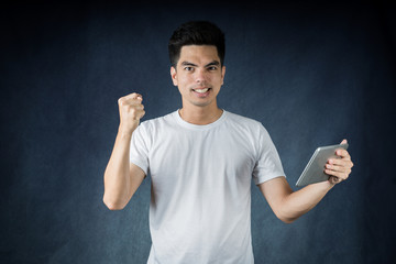 Portrait handsome young asian man wearing a white shirt holding smart phone or tablet excitement or celebrating his victory sign isolated on white background. Asian man people.
