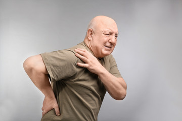 Senior man suffering from pain in shoulder on light background