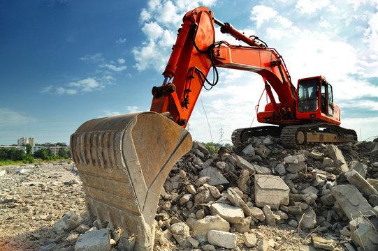 Crawler excavator on demolition site. Front view of a big crawler excavator working on demolition site.