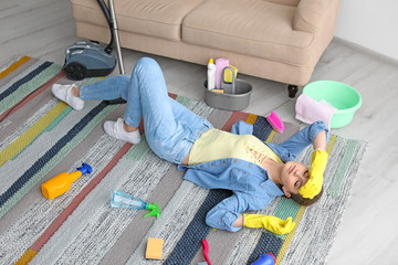 Tired woman with cleaning supplies lying on carpet at home