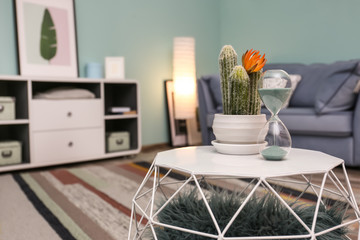 Stylish table with hourglass and cactus in living room
